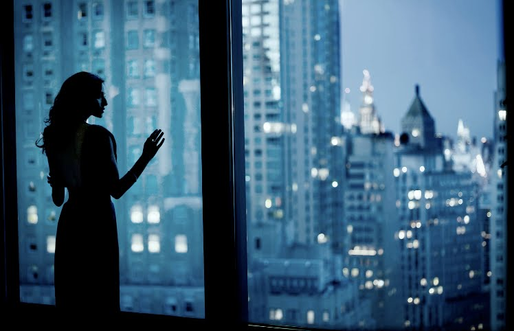woman-looking-out-windows-urban-city